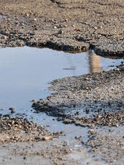 Potholes come out in full force in Lansing on Saturday,