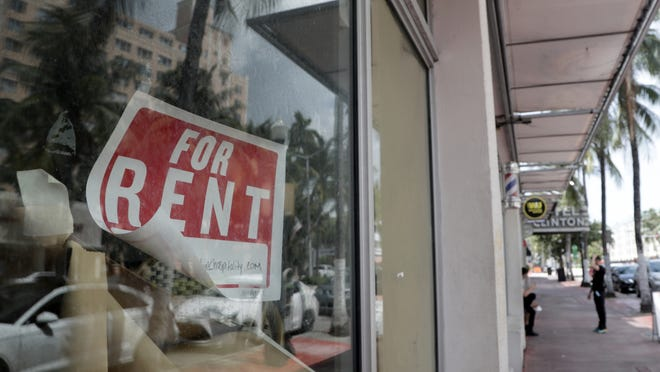 A For Rent sign hangs on a closed shop during the coronavirus pandemic in Miami Beach, Florida.