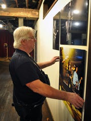 """Photographer Carl Dunn studies the layout of his photography exhibit, """"This is Rock & Roll,"""" at the 9th Street Studios. The event will be Saturday, April 15, from 3 p.m. to midnight and Sunday, April 16, from noon to 6 p.m."""