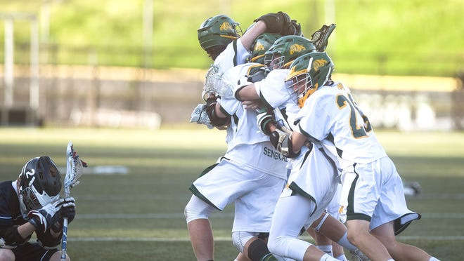 Burr and Burton players pile onto Max Pagnucco after he scored the overtime game-winner against Burlington in the Division II boys lacrosse championship game on Thursday at Castleton State College.