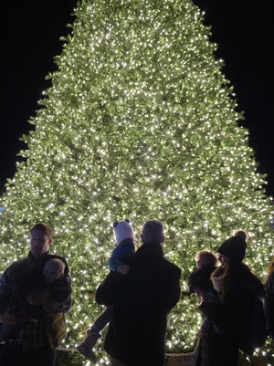 People gather around the City of Franklin's Christmas tree after a tree lighting ceremony on Thursday, Dec. 1, 2016, on the downtown Franklin square