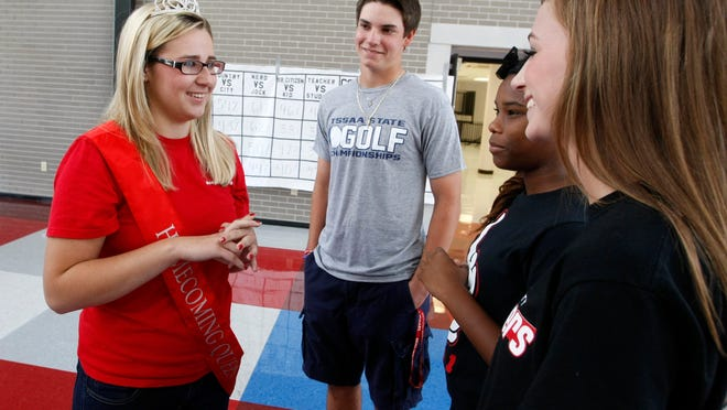 Ashley Travis, left, visits with classmates Clayton Walker, Terrah Black and Olivia Sleigh. The Montgomery Central senior was tabbed homecoming queen Friday night. One year ago, she was still fighting for her life after being involved in a critical car wreck.
