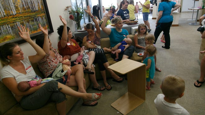 Mothers raise their hands as their babies latch on and breastfeed during the The Big Latch On St. George event held at the Dixie Regional Health and Performance Center Saturday, August 2, 2014.