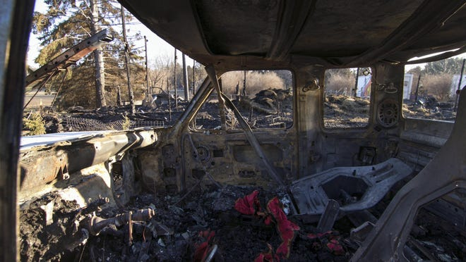 The charred remains of a barn can be seen through a gutted truck attached to a horse trailer at a farm in Putnam Township, Mich. Authorities say seven horses died Sunday, Jan. 13, in the barn fire at a farm in southeastern Michigan.
