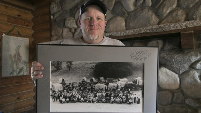"""In this Monday, Jan. 14, 2019 photo, Kenny Lindsay, owner/auctioneer of Kenny Lindsay's American Eagle Auctions and Appraisals Co., holds an original cast and crew photo from the production of the television show, """"Little House on the Prairie,"""" in Genoa Township, Mich. The photo sold for $1200 to the Laura Ingalls Wilder Museum from the estate of Melissa Gilbert and Timothy Busfield."""
