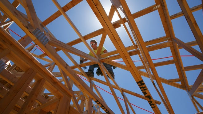 Danny Pledger works on framing the roof Monday on a home in Little Valley. Single-family residential building permits in St. George picked up in April and May, and year-to-date the total of 210 is close to 2013's total of 234.