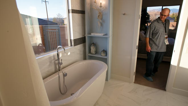 "A visitor to the St. George Area Parade of Homes entry called ""The True Home"" looks through the master bathroom in the home Friday, Feb. 13, 2015 on the opening day of the 2015 parade."