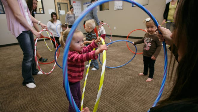Children and their parents play with hoops during a Kindermusic class at The Learning Center for Families Tuesday, Feb. 17, 2015.