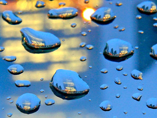 The Northwestern Mutual Life Insurance tower is seen reflected in rain drops Tuesday in Milwaukee. A flood warning remains in effect for Milwaukee, Racine and Kenosha counties through 9:45 p.m. Tuesday as an additional round of rain soaks the region.