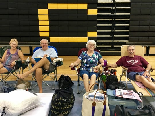 Two families from the Spanish Lakes community in Port St. Lucie, Katherine and Joe Kelly, along with Kathy and Bob, take it easy Thursday morning at the emergency shelter located at Treasure Coast High School in Port St. Lucie.