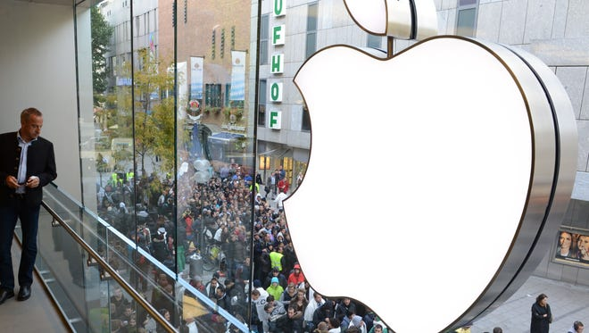 Customers line up to enter the Apple Store  in the southern German city of Munich.