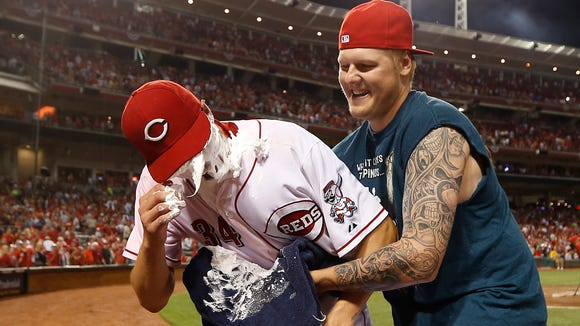 Reds starting pitcher Homer Bailey (34) gets a face full of shaving cream from teammate Mat Latos after Bailey pitched a no-hitter against the Giants at GABP last July.