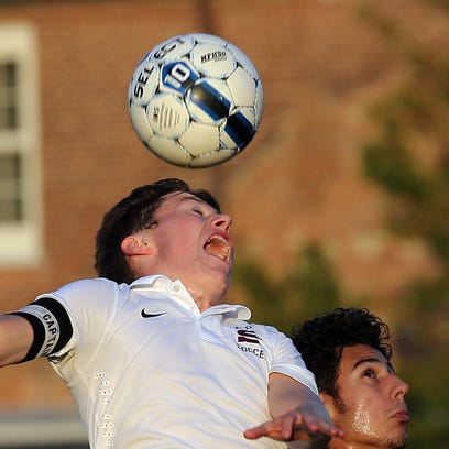 Scarsdale's Max Bryant (4) heads the ball away from