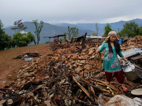 A woman recovers cooking pots from her collapsed home destroyed village of Paslang near the epicenter of Saturday's massive earthquake in the Gorkha District of Nepal on Tuesday.