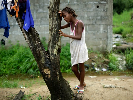 In this Thursday Oct. 2, 2014 file photo, Mercy Kennedy, 9, cries as she learned her mother has died, outside her home in Monrovia, Liberia.
