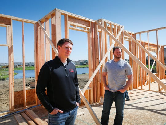 Brothers Josh and Seth Moulton discuss building plans at one of their developments in Ankeny. The Ankeny-based company was one of two Iowa companies named in  Builder magazine's top 200 list.