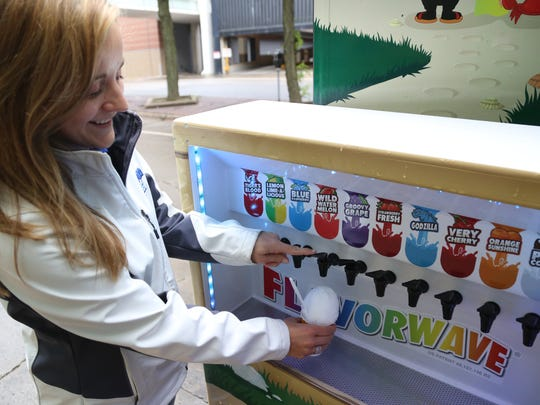 "Brooke Bensema demonstrates the self-serve ""Flavor Wave"" on the Kona Ice truck."
