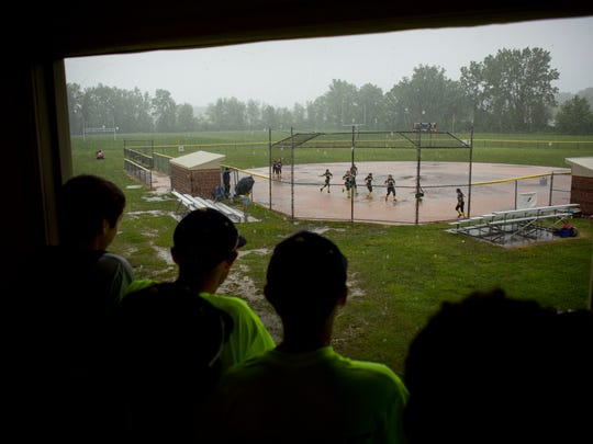 People watch from the concession stand as Algonac softball players runs the bases and play in the mud after their division 2 softball final was cancelled from the storm Saturday, May 30, 2015 at Algonac High School.