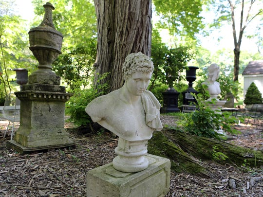 """Most of the inventory of garden antiquities is in a display area behind the house. In the foreground is a classical style composition stone bust marked """"Papini A"""" for the Giacomo Papini firm, Italian, c.1930. Behind it is a Cotswold stone finial, English, c.1870, once part of a larger architectural piece."""