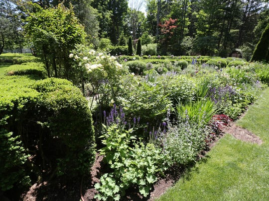 Old boxwood hedges line the edges of the perennial border.
