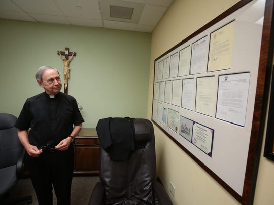 Father Howard A. Lincoln of Sacred Heart Church in Palm Desert shows off the rejection letters to different seminary that he applied for he has mounted on the wall.