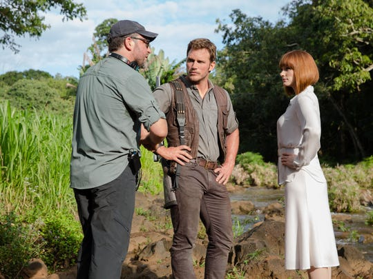 """From left, Director Colin Trevorrow, Chris Pratt as Owen and Bryce Dallas Howard as Claire on the set of """"Jurassic World."""" Steven Spielberg returns to executive produce the long-awaited next installment of his groundbreaking """"Jurassic Park"""" series. Trevorrow, of Burlington, directs the epic action-adventure, and Frank Marshall and Patrick Crowley join the team as producers."""