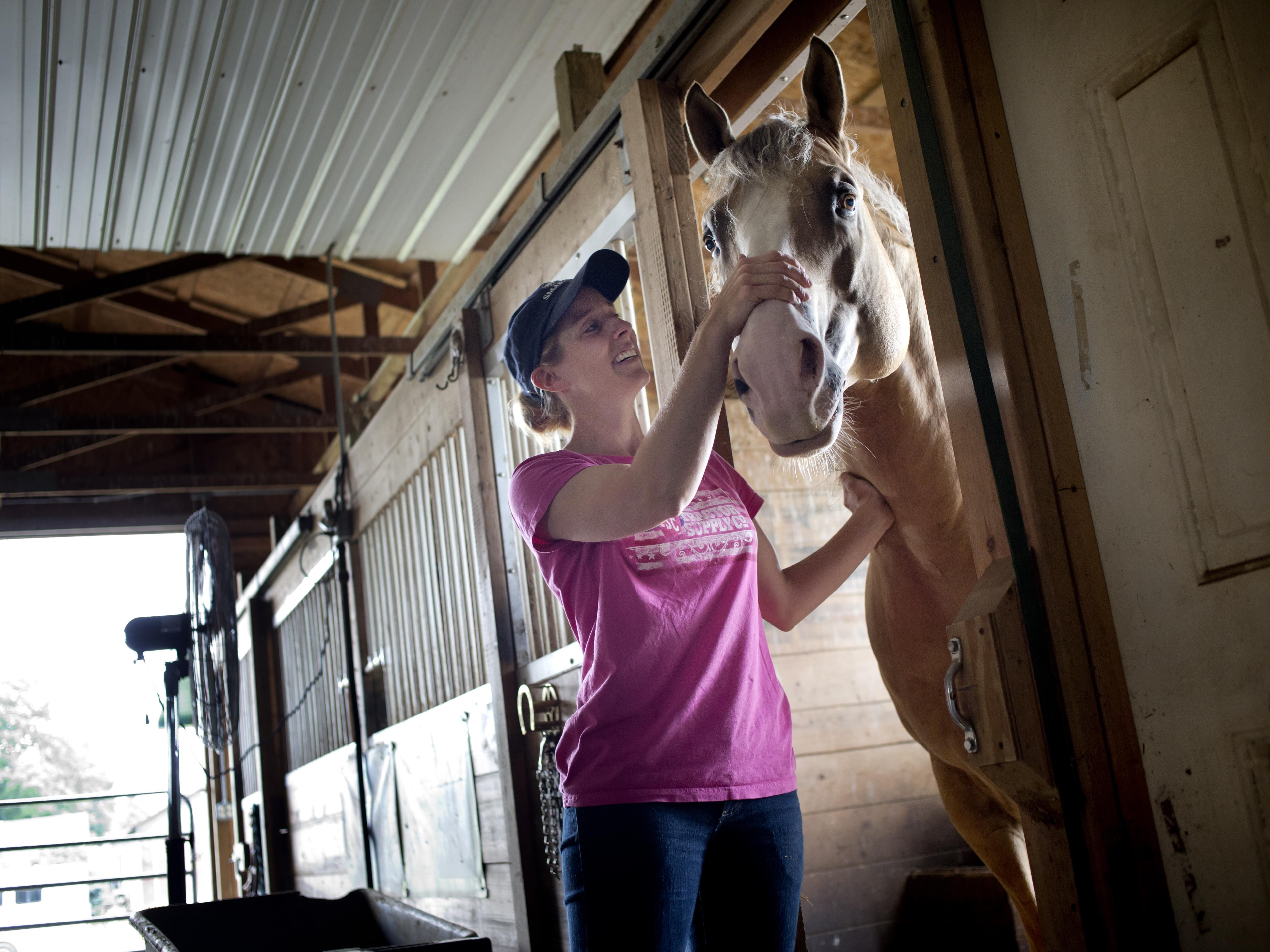 Marine City girls track coach Kristen Humble checks on one of her 20 horses Wednesday at her home and ranch in Clyde Township.