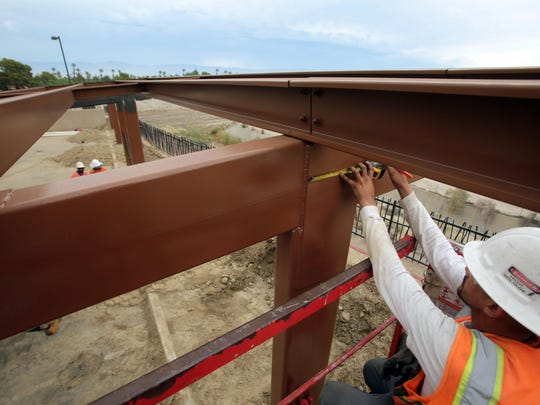 Jose Casillas, of Indio, works to build a solar shade structure for the parking lot at the Rancho Mirage Public Library on July 1, 2015.