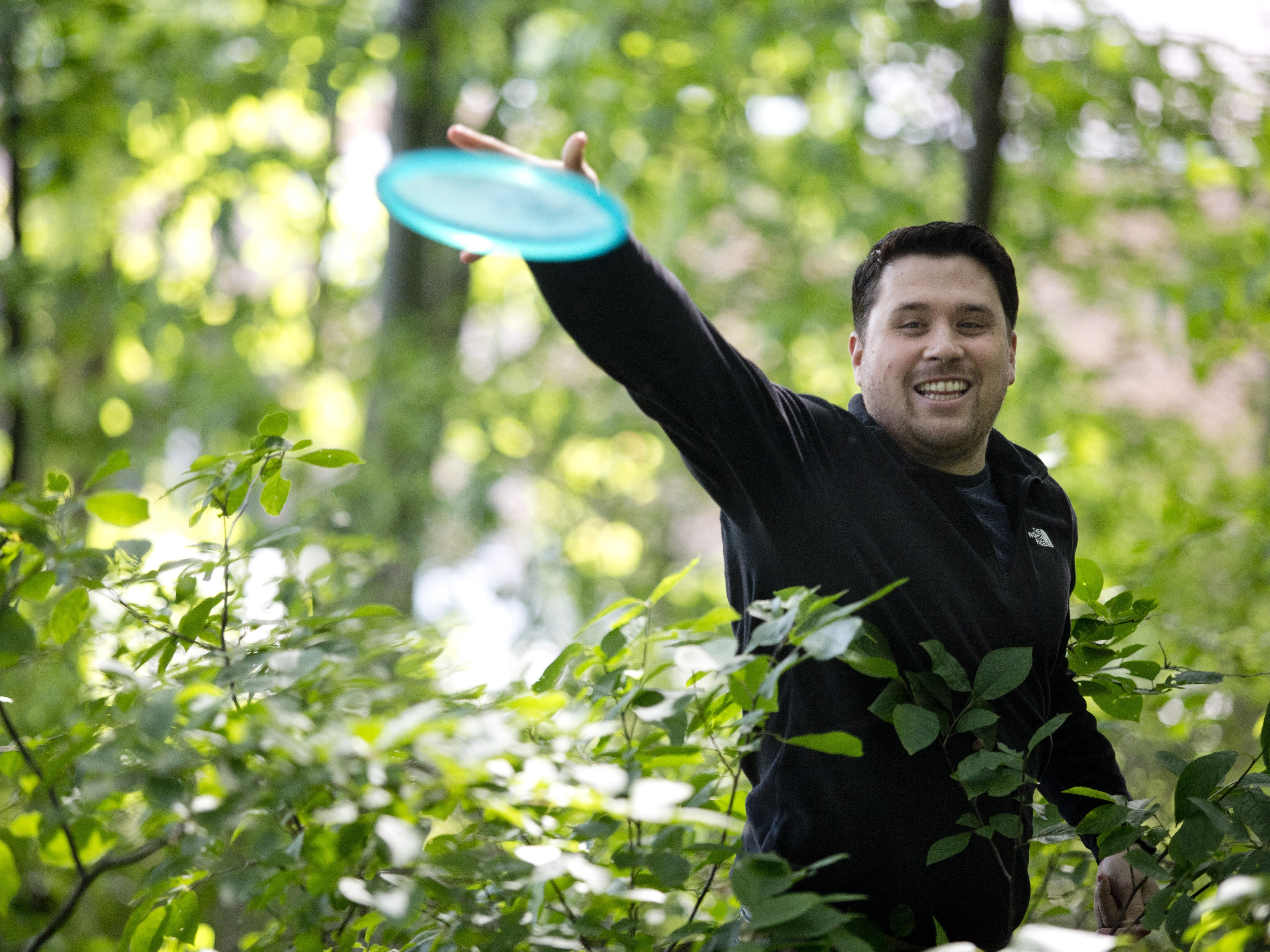 Paul Costanzo throws a disc over an area of brush while playing disc golf Friday, July 3, 2015 at Holland Woods in Port Huron.