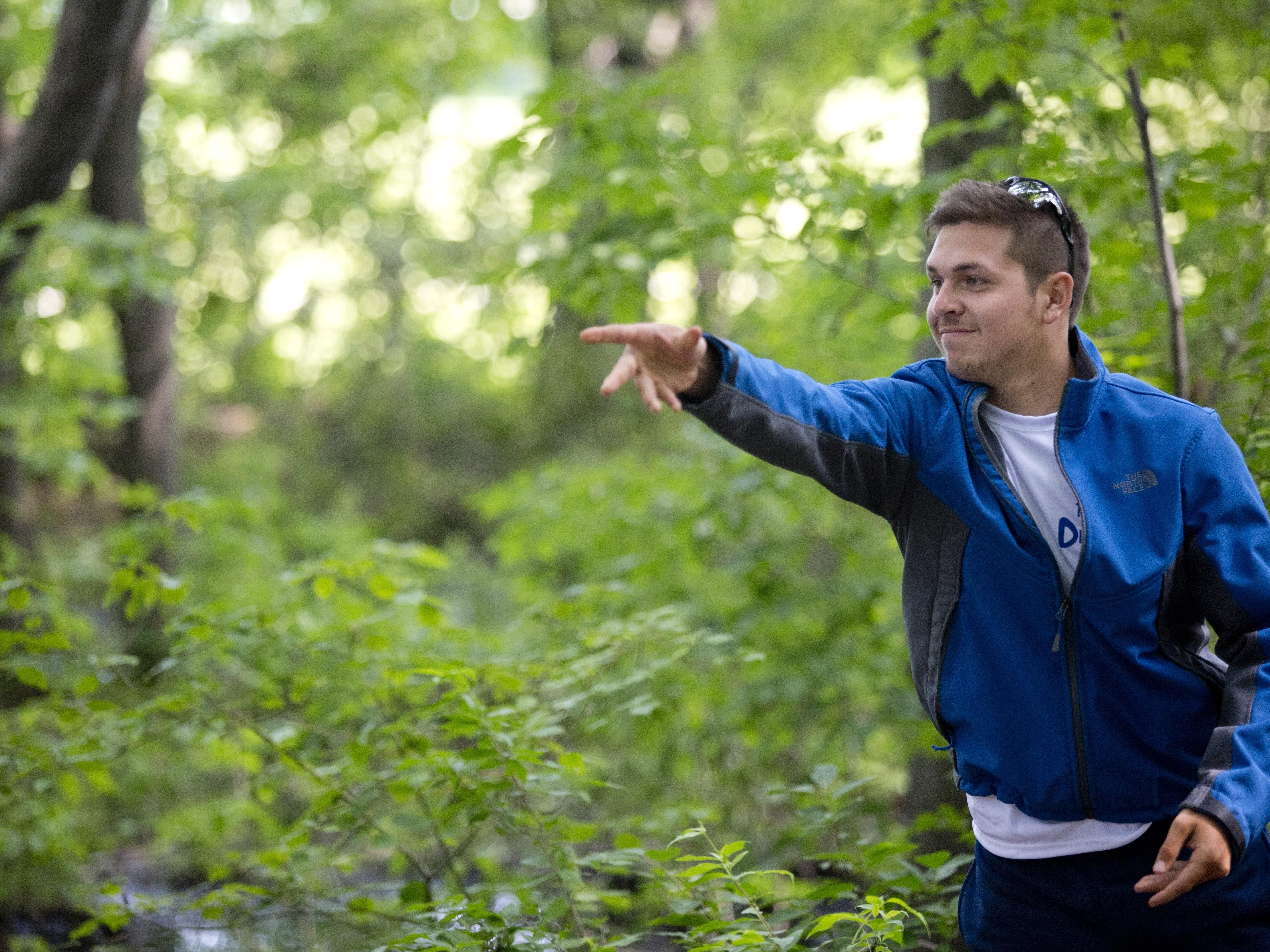 Felipe Macias, of Yale, watches his disc while playing disc golf Friday, July 3, 2015 at Holland Woods in Port Huron.