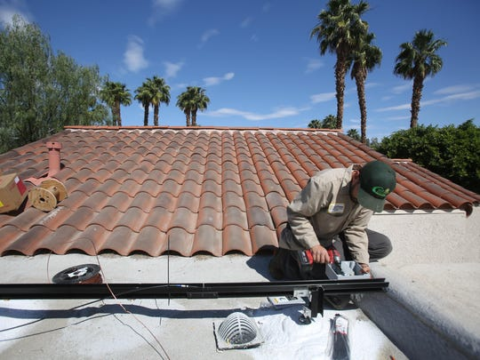 J. Omar Ornelas/The Desert SunHelioPower employee Nick Dean installs solar panel racks at a Rancho Mirage home. HelioPower employee Nick Dean, installs racks to be used for solar panels at a home in Rancho Mirage.