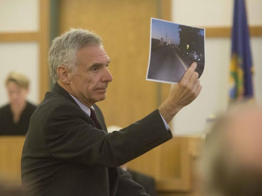 Deputy Franklin County State's Attorney John Lavoie holds up a picture during opening statements Wednesday in the murder trial of Matthew Webster that shows the scene where Anna Alger was shot and killed in St. Albans in September 2013. The authorities say the attack was related to road rage. Webster has pleaded not guilty to a murder charge. His defense is focusing on issues of his mental health.