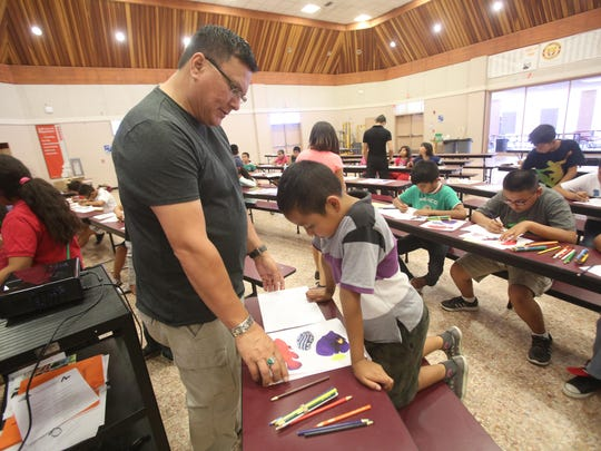 Educator Simon Silva helps Angel Candelario with ideas on a drawing at Toro Canyon Middle School in Thermal as part of a student and parent workshop offered to migrant farmworker families.