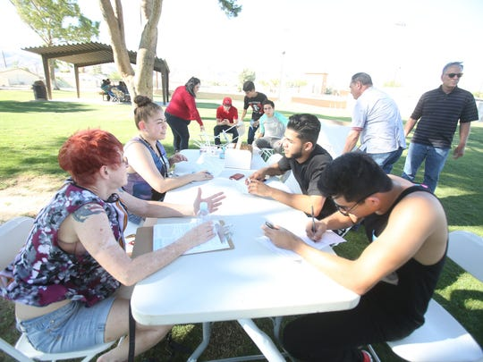 Desert Hot Springs residents Osvaldo Espinosa, 22 sitting at bottom right and Juan Aguilar, 19 register to vote as part of a Southwest Voter Registration Education Project event held at Wardman Park on Saturday. The organization hopes to register Latinos to vote.
