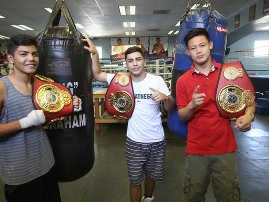 From far right, Brandun Lee, Anthony Reyes and Rommel Caballero all placed first during the 2015 Desert Showdown amateur boxing competition.