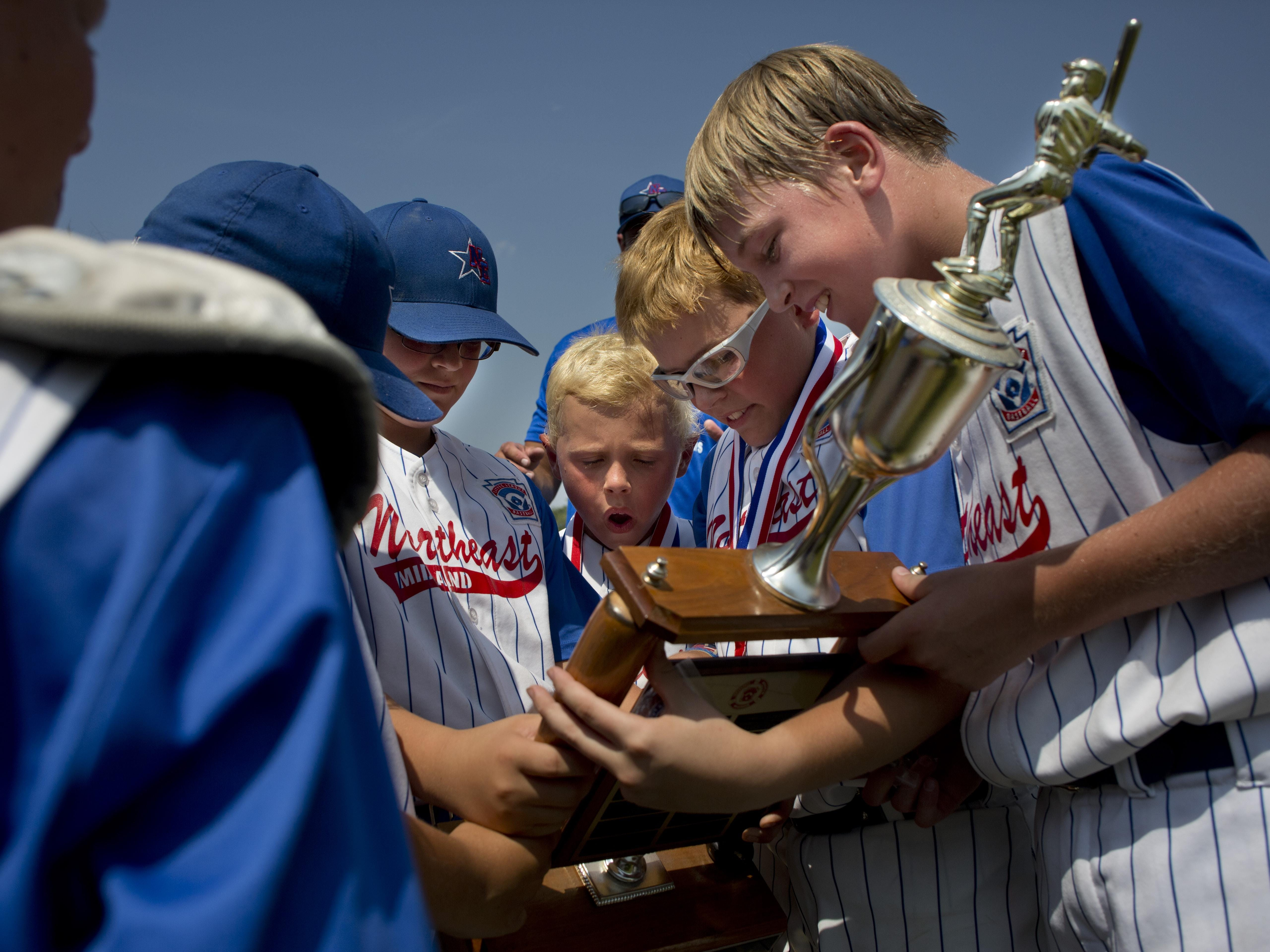 Midland Northeast players check out the trophy after beating Bay City Northwest in a state final 10-and-under baseball game Wednesday in St. Clair.