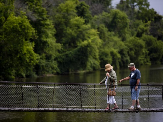 People walk across the Black River during the Swinging Bridge Festival Saturday, Aug. 1, in Croswell. The bridge, built in 1905, is the only pedestrian suspension bridge in Michigan.