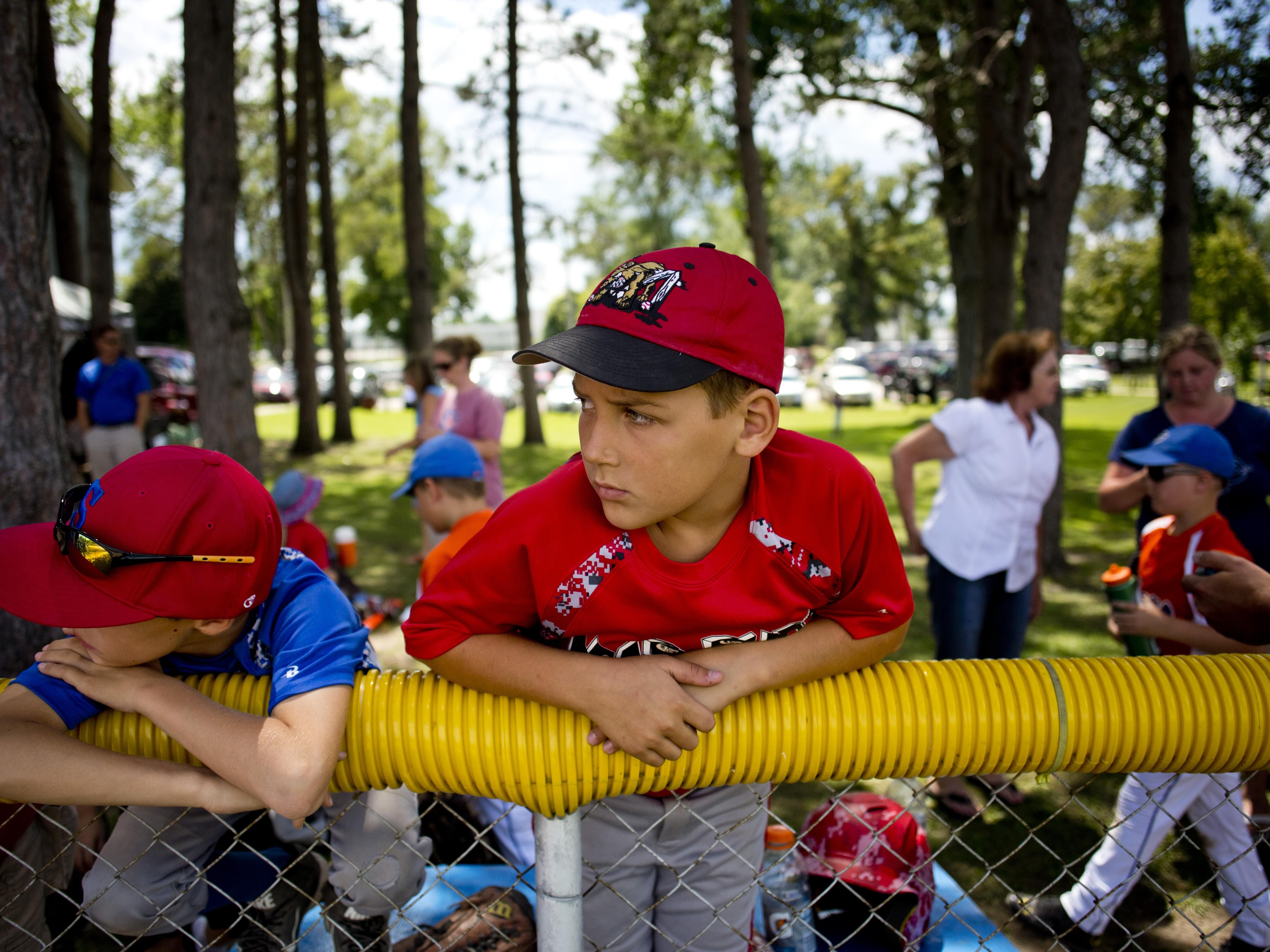 St. Clair player Conner Shurkey, 9, watches from the fence during a Little League skills competition Saturday, August 1, 2015 at Marysville City Park.