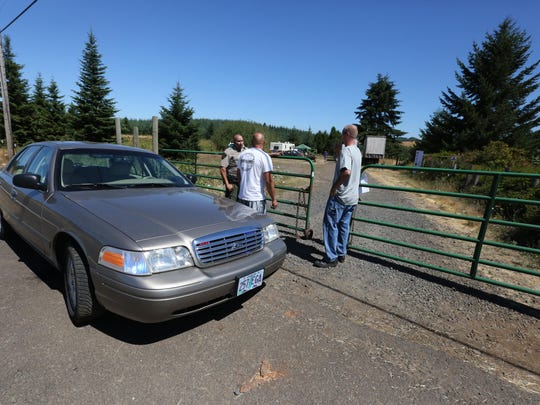 """Ollie Zeek, center, speaks with Marion County Sheriff's Office Dep. Mike Bell on Friday, Aug. 7, 2015, at the entrance to a Silverton area farm where """"Boombox in da Boondox"""" rave was scheduled to be held."""