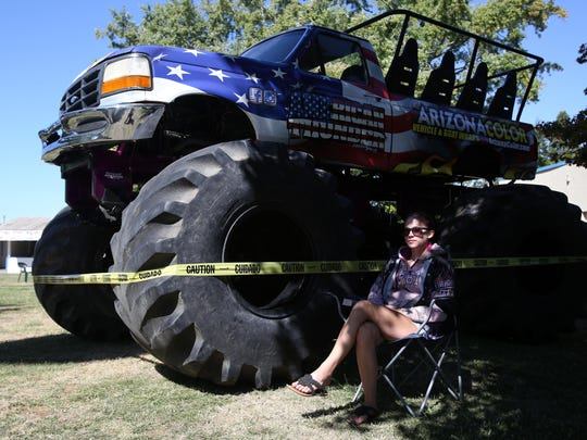 Kendra Leach, of American Thunder Motorsports, sits next to a monster truck that will be giving free rides to visitors at The Polk County Annual Fair on Saturday from 5 p.m. to 10 p.m. Photo taken on Friday, Aug. 7, 2015, in Rickreall, Ore.