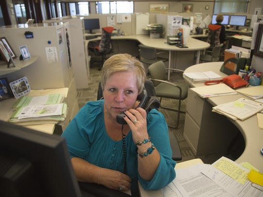 Teresa Dowd helps a customer on the phone at Farm Credit Services of America in Perry, Iowa, Monday, Aug. 10, 2015.