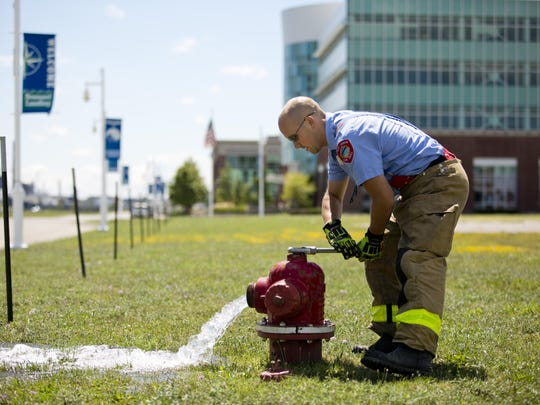 Firefighter Rob Montgomery opens a hydrant during training on Third Street in Port Huron in 2015.