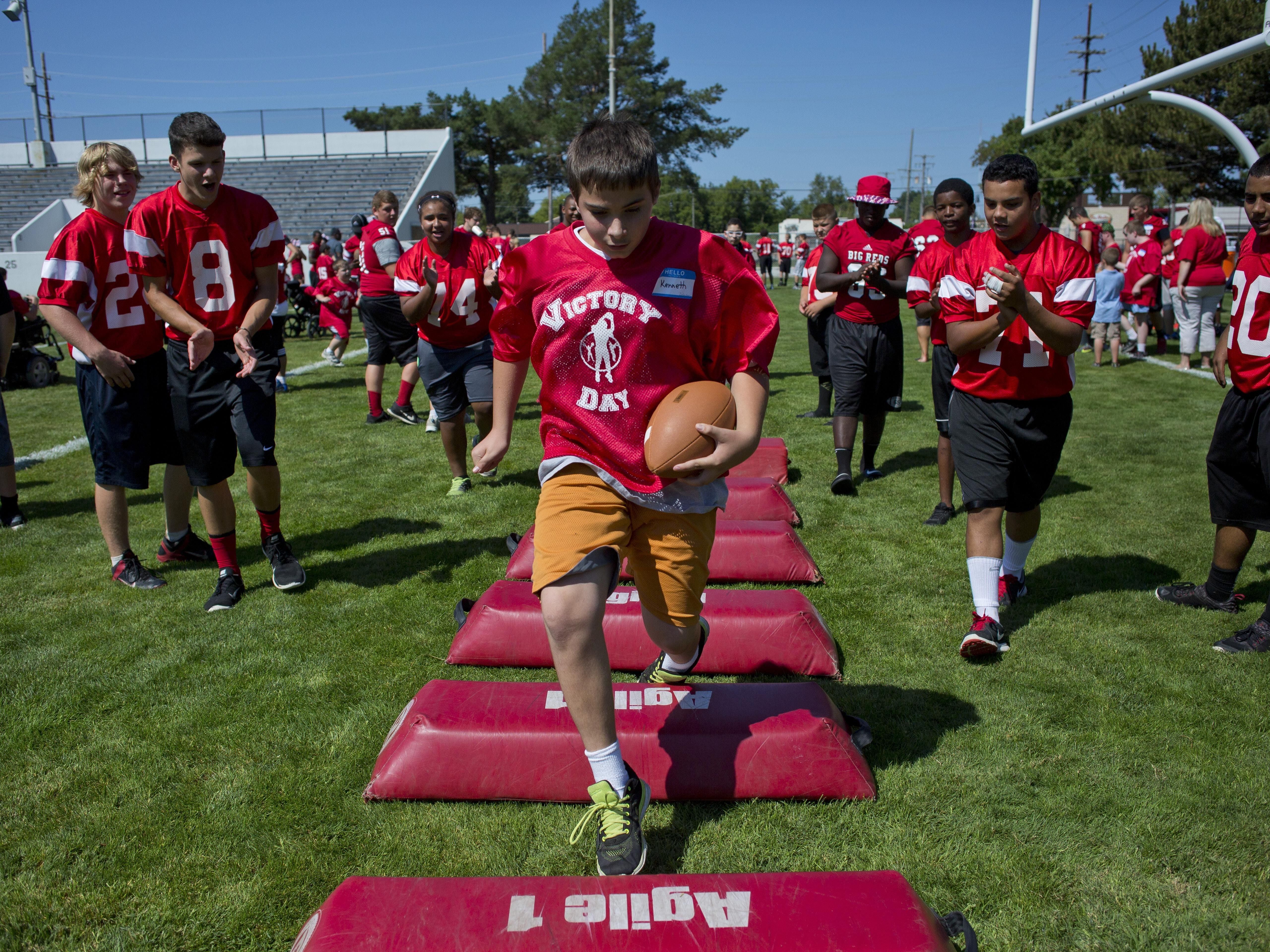 Kenneth Zehnder is cheered on as he runs the ball through obstacles during Victory Day Saturday, August 15, 2015 in Memorial Stadium at Port Huron High School. The event paired special needs students with mentors from the football and cheerleading teams.