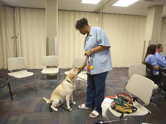 Arlecia Kelly, a mentor for other women at the California Institute for Women, also helps trains service dogs at the institution.