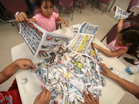 Sisters Julie, 7, and Sofia Romero, 4, tear up newspaper to make paper mache masks during an art party at the Cathedral Center on Saturday. The masks will be worn by children in a parade as part of the Taste of Jalisco Festival in November.