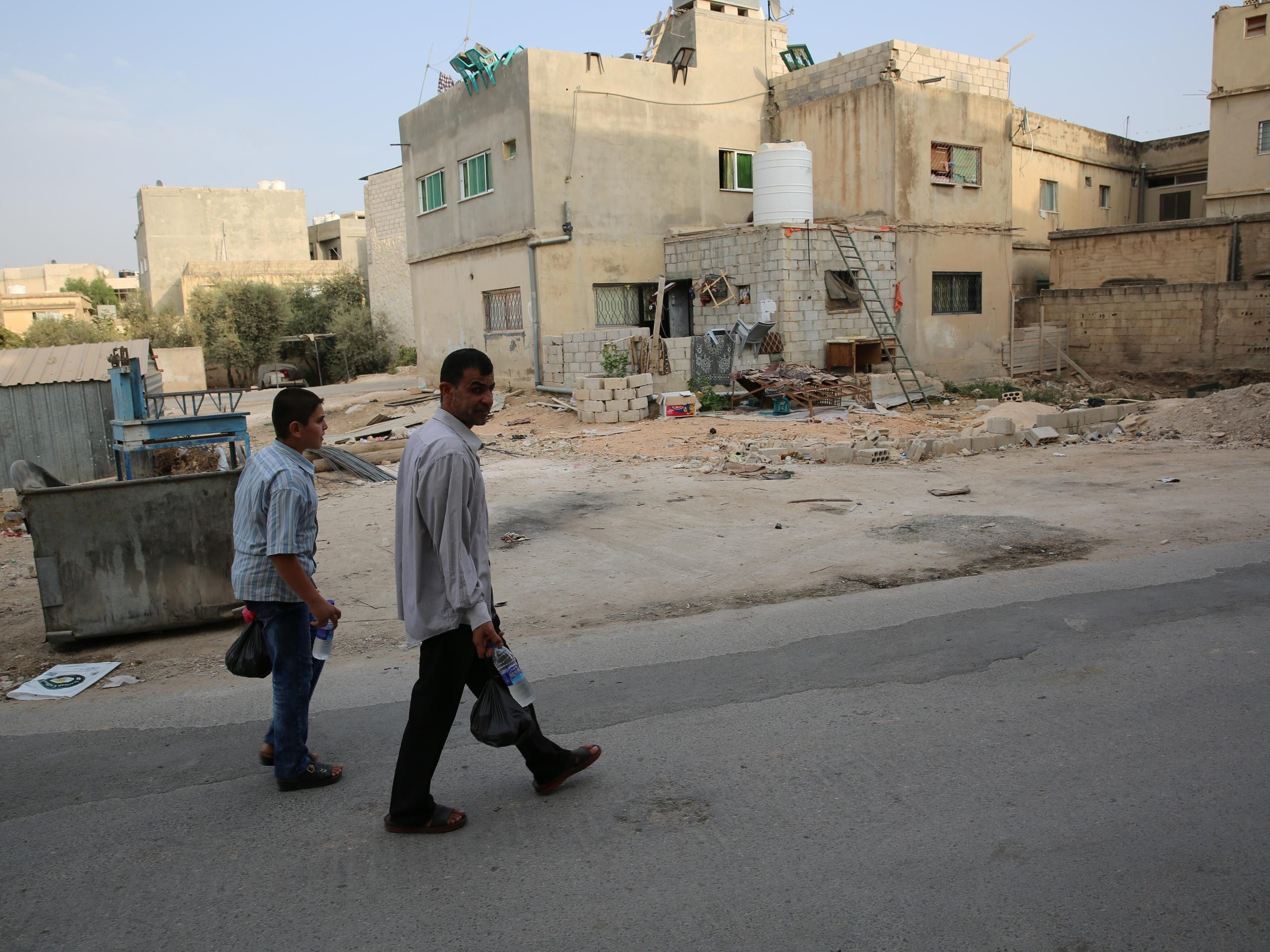 Ahmad Al Tybawi and his eldest son, Abdulbaset, take groceries home through their Jordanian town of Taiyyba.