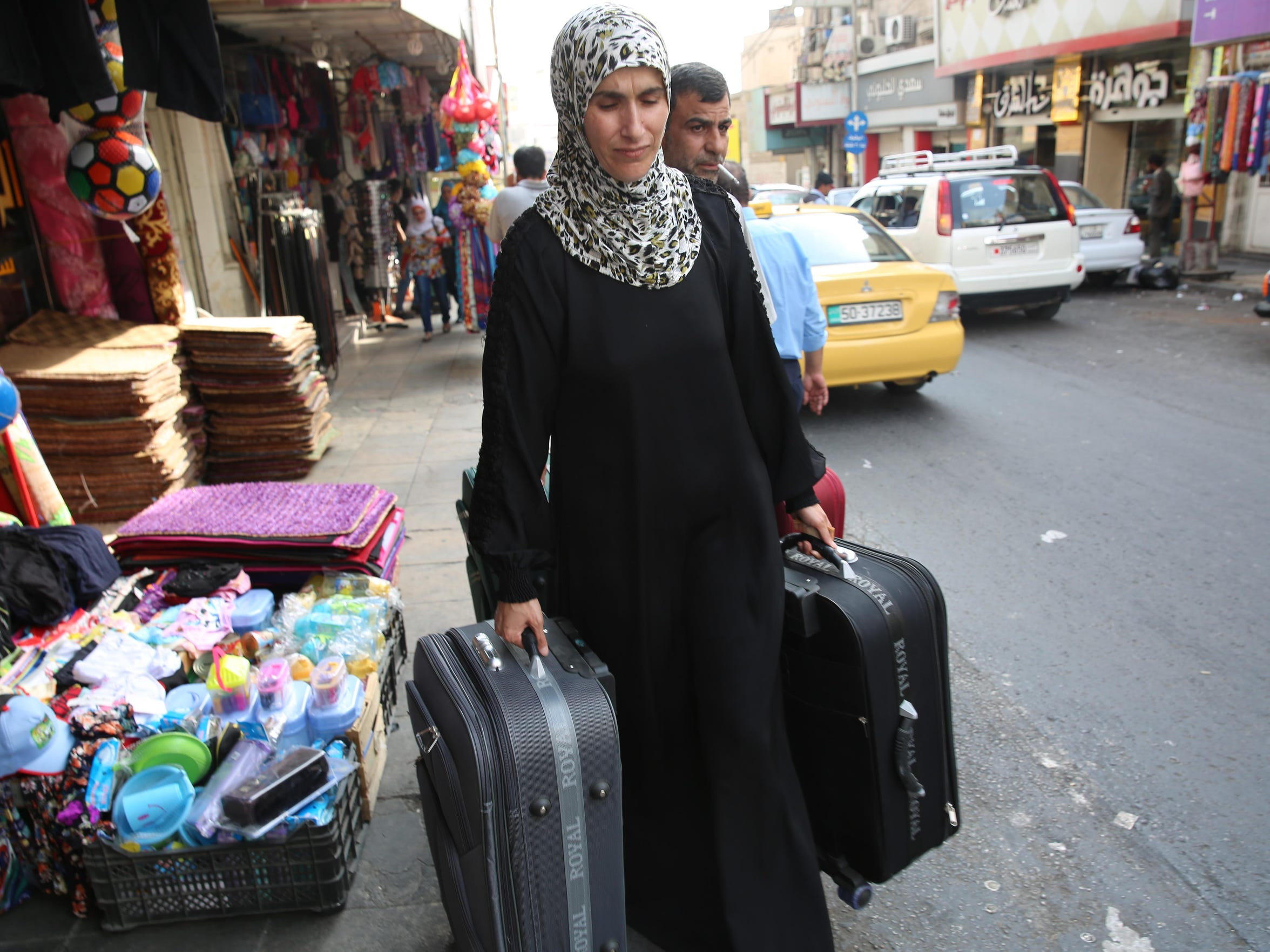 Ahmad Al Tybawi and his wife, Ahlam Al Swedan, carried the bags they'd purchased in the market area of Irbid, Jordan, for their move to the U.S., a rare shot at resettlement.