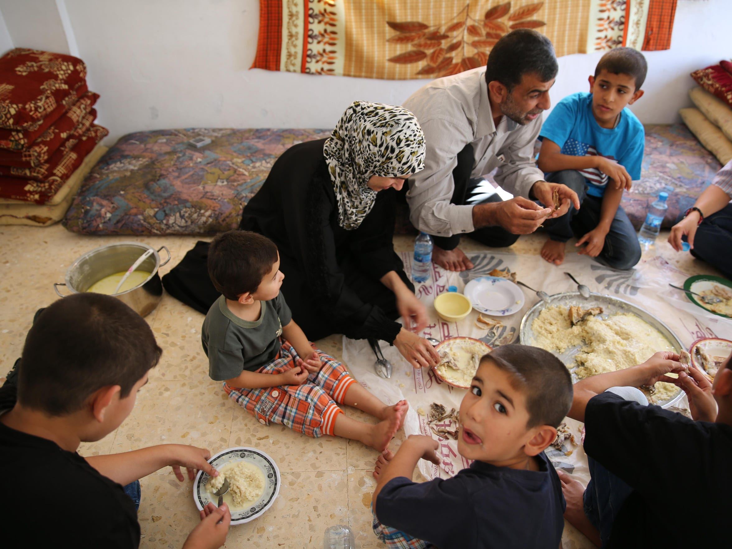 . In their sparse Taiyyba apartment, Ahmad Al Tybawi and his family share a celebratory meal, a treat after scraping by for years on dwindling humanitarian aid and illegal day labor jobs.