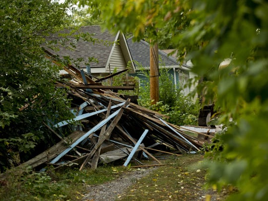Debris from a garage fills an alley way as crews from Torello Demolition clear the site of a home Tuesday, September 29, 2015 at 1216 Division Street in Port Huron.