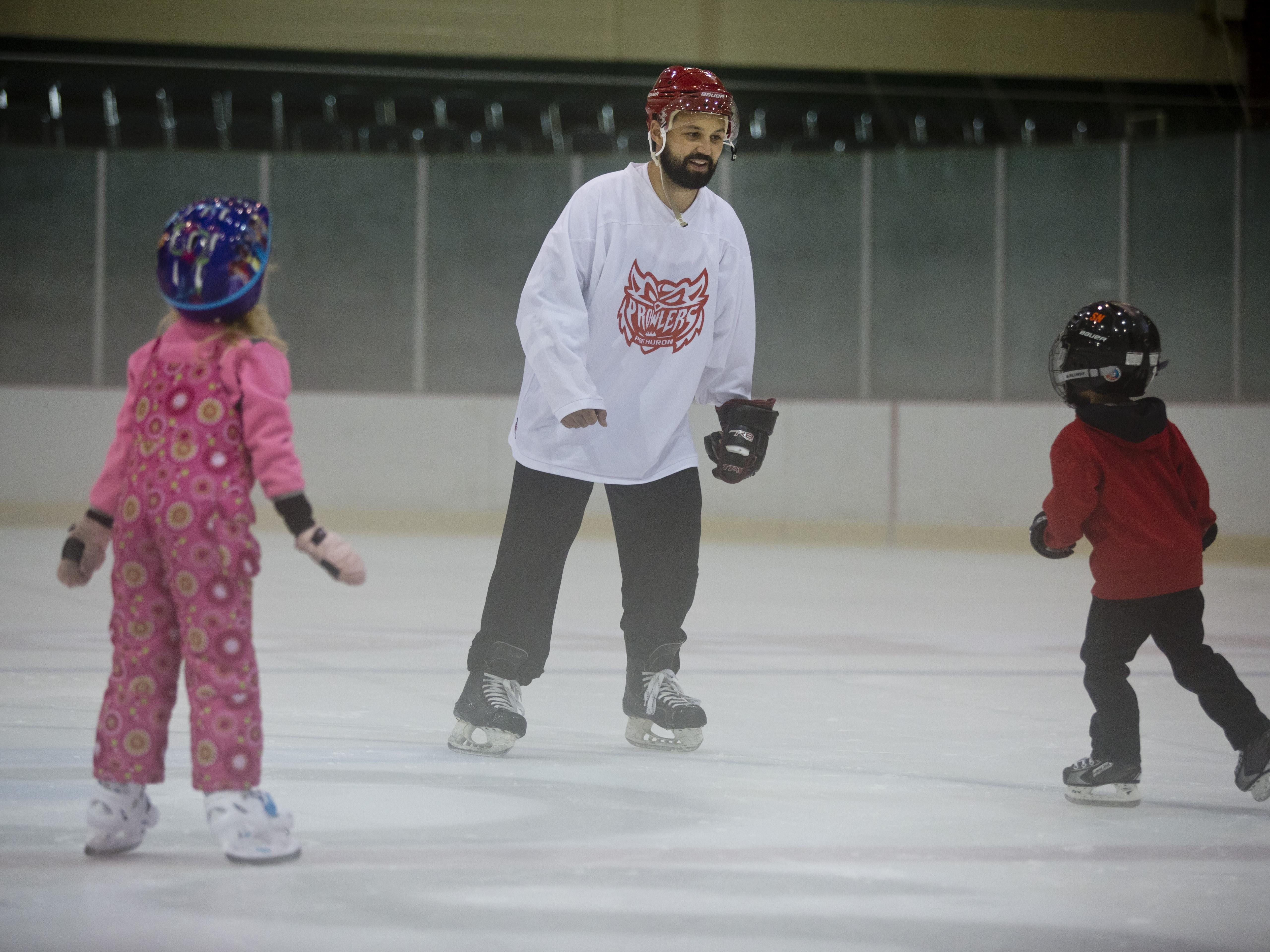 Port Huron Prowlers assistant coach and player Joe Pace works with Tori Stein, 6, and Brayden Nichols, 5, during a learn to skate program Wednesday, October 7, 2015 at McMorran Arena.